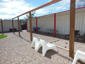 Shipping containers are used to create this covered outdoor recreation area.